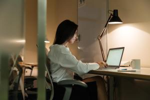 Serious young businesswoman working and using blank screen laptop in office