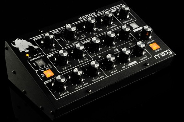 Moog minitaur bass synth and manual power suppy and wooden checks.