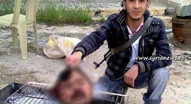 A member of the FSA grills a head of a decapitated officer - Idleb