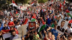 Syrians citizens waving national flags and holding photos of Syrian President Bashar Assad during a pro-government rally in Aleppo province, Syria, April 29, 2014