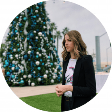 Cause-driven Amelia Thomas is photographed outside by a Christmas tree.