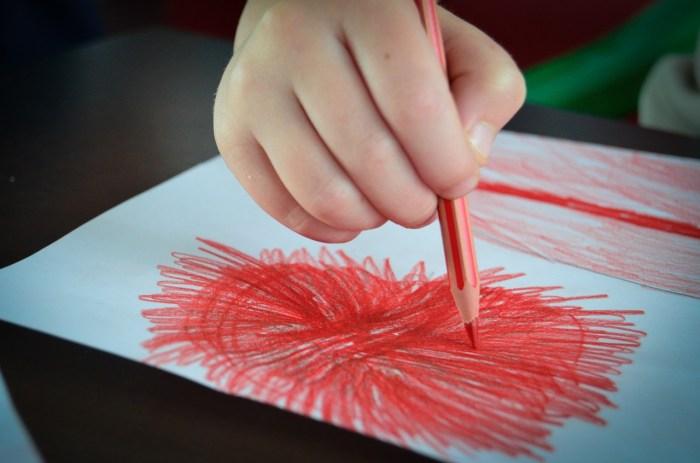 hand met rood potlood tekent op papier