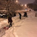 Niños se detienen para ayudar a un hombre en sillas de rueda en la nieve en 2018