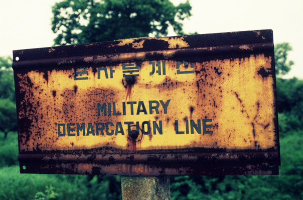 Photo of the Military Demarcation Line (MDL), sign located in the woods at Pan Mun Jom (DMZ), separating North and South Korea.
