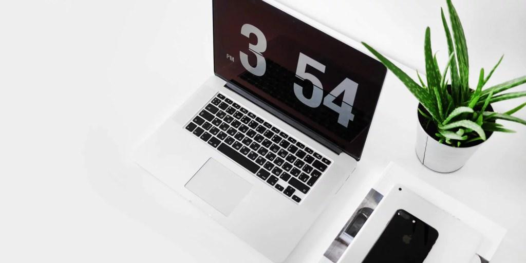 Mesa com Macbook, celular e planta