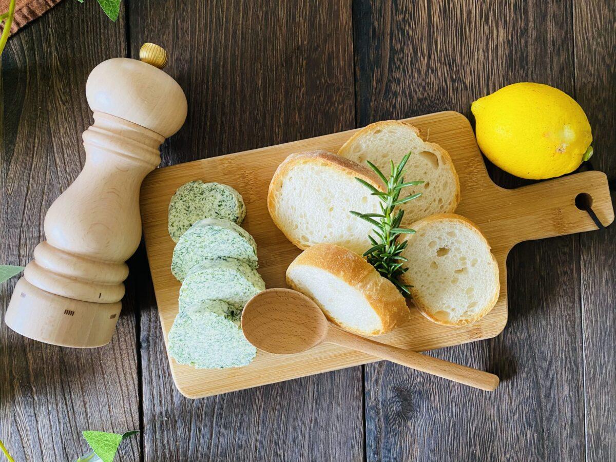 小さい木のボードに並べられたバゲット、ハーブバター、ローズマリー、レモン、ペッパーミル