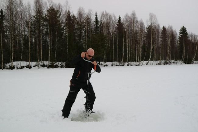 Gat maken in het ijs om te ijsvissen in Zweden