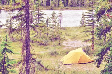 a yellow tent in the forest by a river