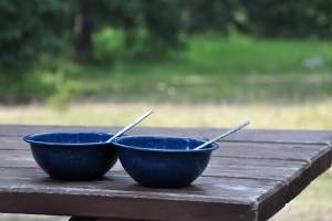 two blue metal camping bowls sitting on a picnic table