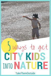 toddler wearing shorts and a sun hat playing in a concrete city splash park. text reads 5 ways to get city kids into nature.
