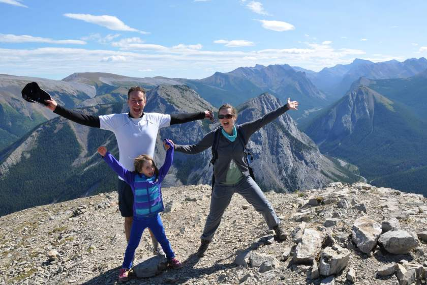 A mom, dad, and young girl standing a top Sulpher Skyline in Jasper National Park