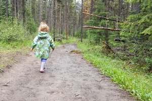 A toddler walking along a muddy path