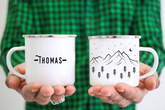 a man with a green plaid shirt holding a personalized enamel mug with mountains and forests