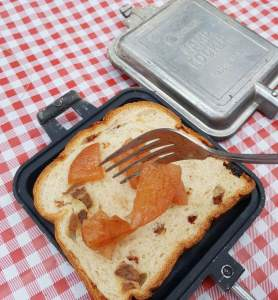 Spooning apple filling onto cinnamon raisin bread to make apple hobo pies