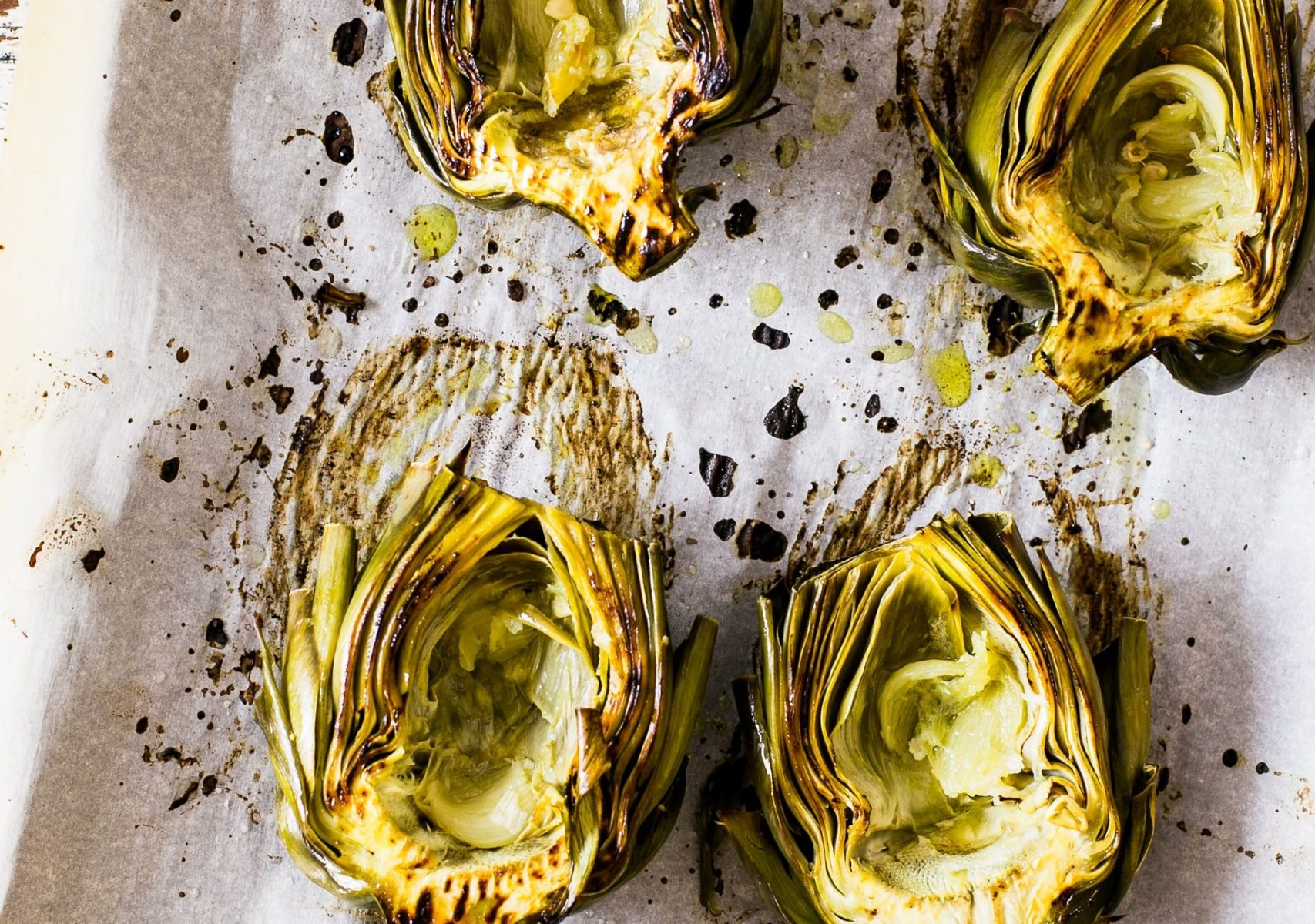Roasted artichoke hearts on a roasting pan lined with parchment paper