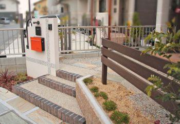 モザイクタイルの門柱とウッドフェンス