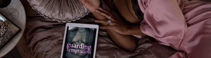 A black woman lies in bed beside an ipad showing the cover of Guarding Temptation, which displays the muscular torso of a black man with the title text in pink