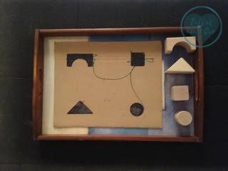 Piezas de construcción de madera (puente, cubo, cilindro y pirámide) con cartón con siluetas dibujadas. Para trabajar emparejando figuras