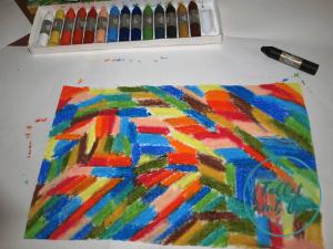Hoja blanca pintada con varios colores y caja de ceras