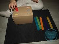 Manos de niña de 22 meses colocando los deprecares en las ranuras