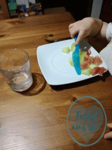 Plato de patatas con jamón y manos de bebé de unos 20 meses cortando con cuchillo de plástico