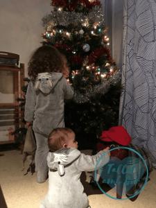 Dos niños con pijama de conejitos vistos desde atrás al lado del árbol de Navidad y el Tió