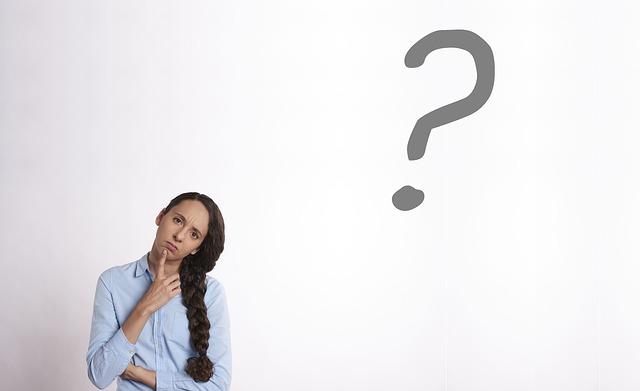 Mujer pensando, con cara de pregunta, e interrogante grande sobre su cabeza