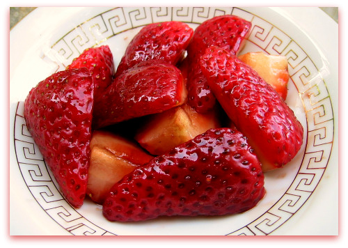 bowl of sliced strawberries with basalmic glaze