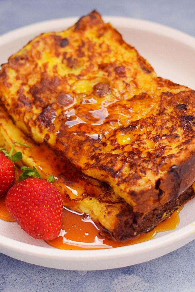 Panettone French Toast on a white plate with strawberries and maple syrup