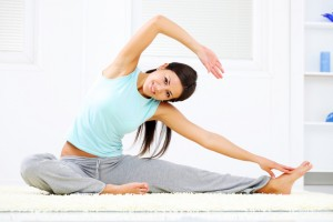 Smiling young woman doing stretching exercise at her home.