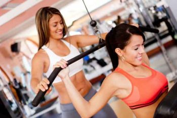Hispanic woman working with trainer in gym