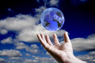 Abstract earth hoovering over an open hand with sky background