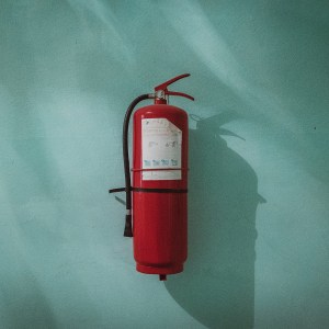 Fire Extinguisher on Green Wall