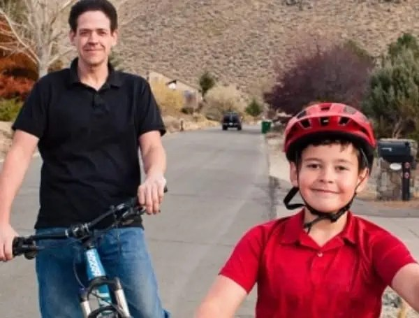 Adam Woodrum and his son, Robert, bike near their home in Carson City, Nevada, on Nov. 7. When Robert fell off his bike in July, he got stitches at Carson Tahoe Regional Medical Center. The family's insurer initially denied the claim. (MAGGIE STARBARD FOR KHN)