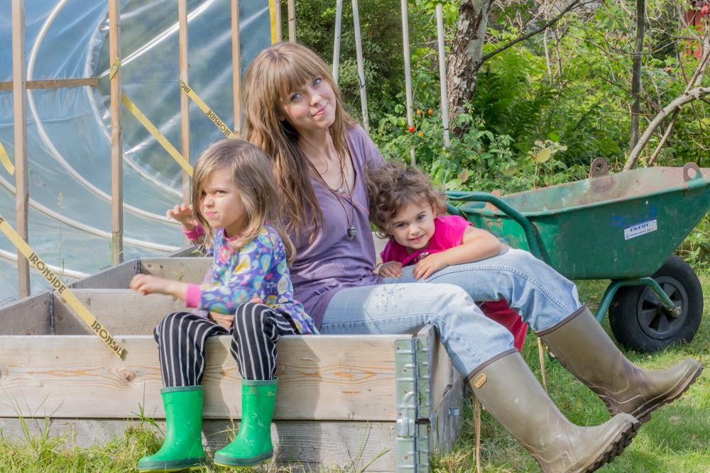 Mamma med döttrar sittandes i en pallkrage bland odlingar i trädgård.
