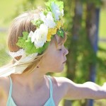 Kind tanzt mit Blumenkranz