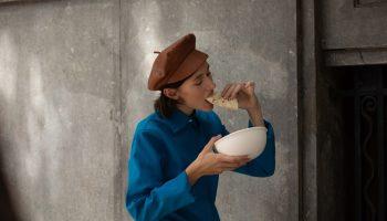mujer comiendose un birrito en la calle, en otoño