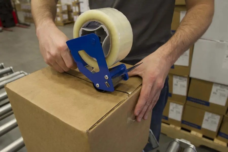 What is the proper way to manually apply packaging tape?