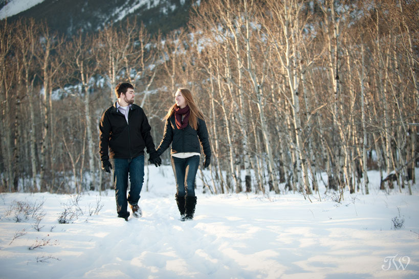 couple stroll in the woods during their winter engagement session