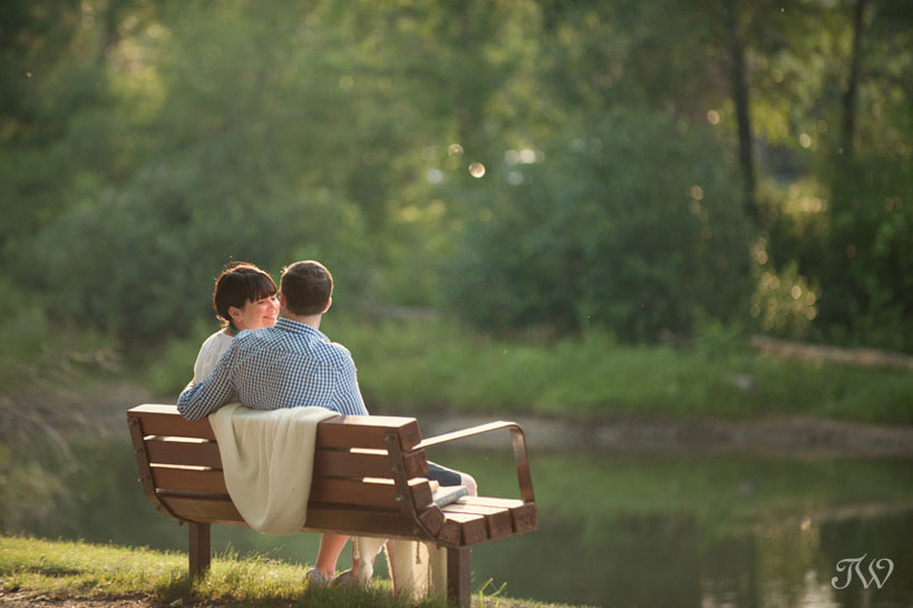 couple sit on a park bench during their engagement session on the Elbow River