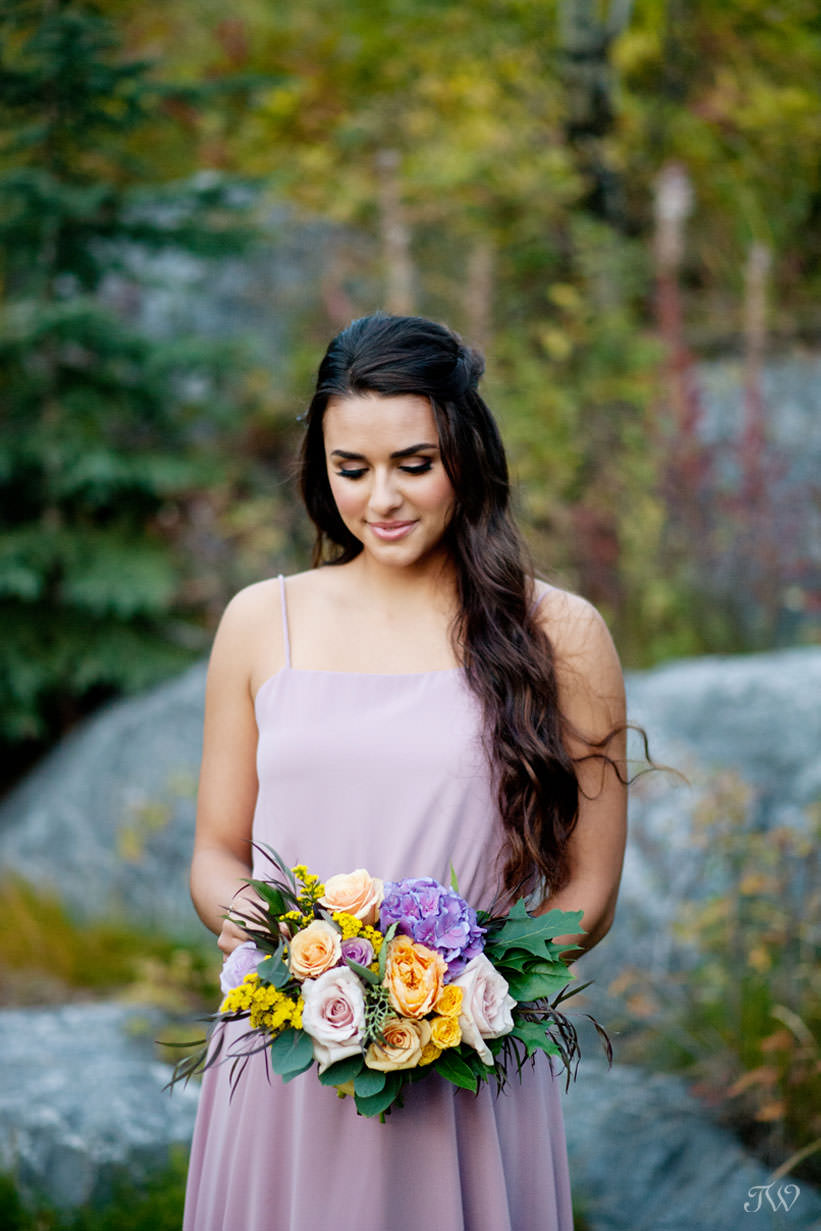 bridesmaid with bouquet from Flowers by Janie captured by Calgary wedding photographer Tara Whittaker