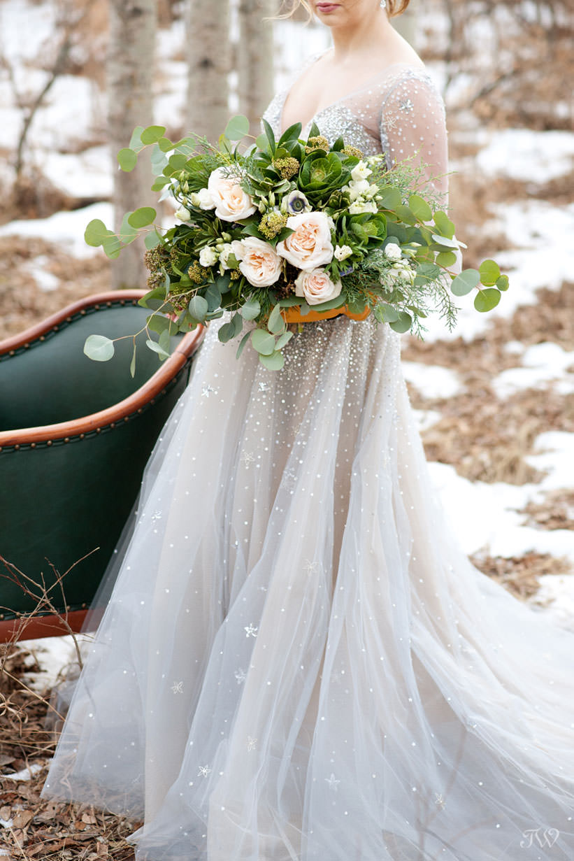 Winter Hayley Paige bride carries bouquet of greenery captured by Tara Whittaker Photography