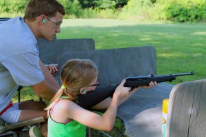 Campers practicing with a .22 rifle under the supervision of a camp counselor