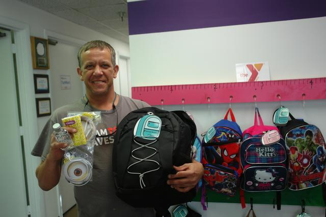 team member with school supplies and backpacks they are donating