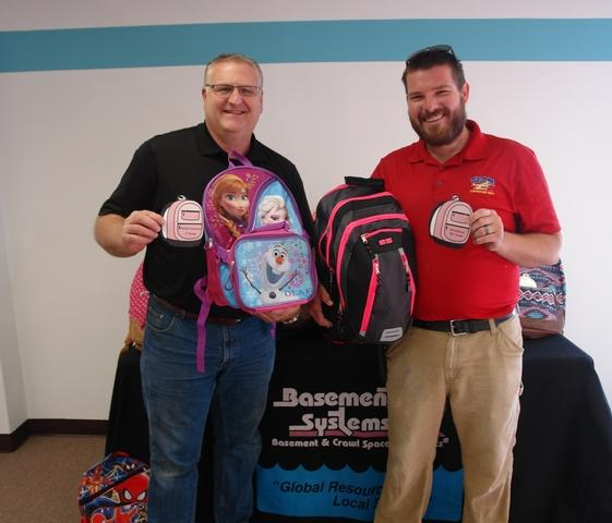 Team showing off all the donated backpacks