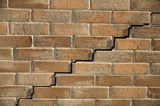 Close up of stair step cracking on brick wall