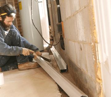 Crew installing interior drainage in basement