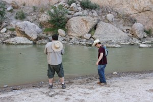 The menfolk throwing rocks into the river