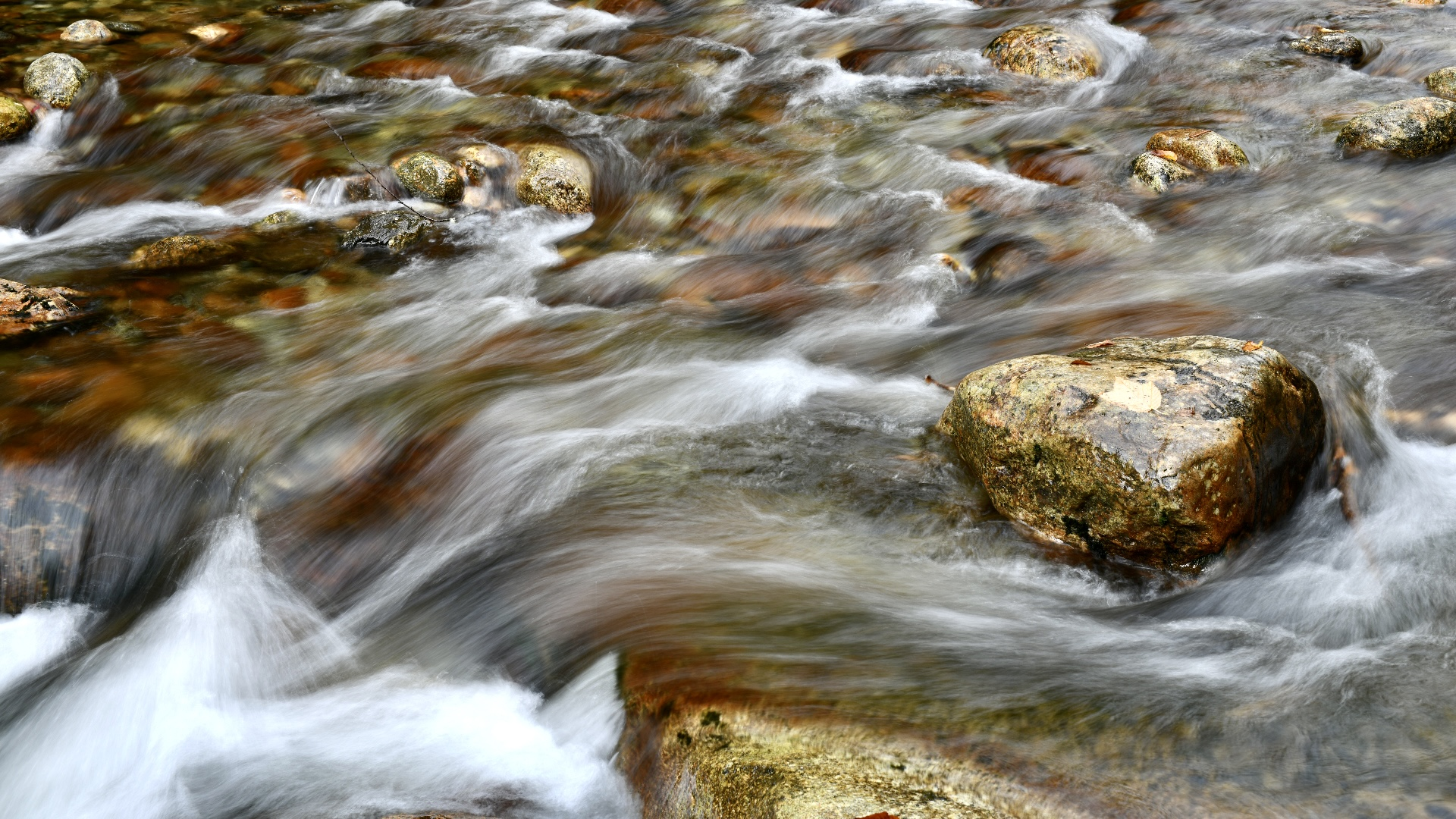 Long exposure of blurred water flowing over river rocks. 2021. Taryn Okesson. Digital Photography. White Mountain National Forest, New Hampshire.