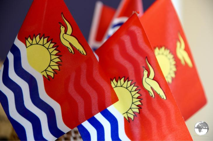 The national flag of Kiribati features a gold Frigate bird flying over a golden sun with three blue/ white bands representing the ocean and the three island groups.